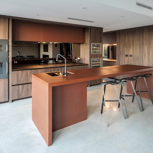Inspiration for a contemporary l-shaped kitchen in Perth with an undermount sink, flat-panel cabinets, dark wood cabinets, stainless steel appliances, concrete floors, with island, grey floor and brown benchtop.