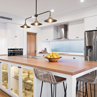 Design ideas for a mid-sized beach style l-shaped open plan kitchen in Perth with a single-bowl sink, shaker cabinets, white cabinets, wood benchtops, white splashback, subway tile splashback, stainless steel appliances, medium hardwood floors, with island, brown floor and brown benchtop.