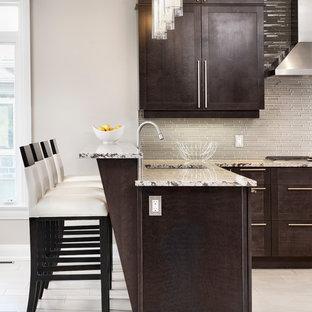 Cette image montre une très grand cuisine américaine minimaliste en U avec un évier encastré, un placard à porte shaker, des portes de placard grises, un plan de travail en granite, une crédence beige, une crédence en carreau de verre, un électroménager en acier inoxydable, un sol en carrelage de céramique et une péninsule.