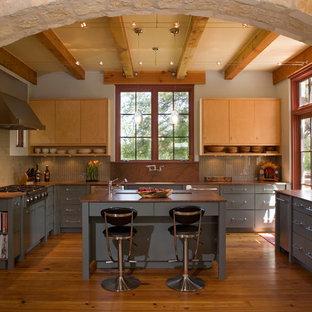 オースティンの中サイズの地中海スタイルのおしゃれなキッチン (アンダーカウンターシンク、フラットパネル扉のキャビネット、淡色木目調キャビネット、グレーのキッチンパネル、シルバーの調理設備の、無垢フローリング、木材カウンター、セラミックタイルのキッチンパネル) の写真