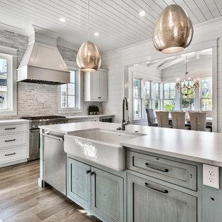 マイアミの中くらいのビーチスタイルのおしゃれなキッチン (エプロンフロントシンク、シェーカースタイル扉のキャビネット、白いキャビネット、グレーのキッチンパネル、シルバーの調理設備、茶色い床、白いキッチンカウンター、珪岩カウンター、石タイルのキッチンパネル、淡色無垢フローリング) の写真