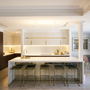 This is an example of a contemporary l-shaped eat-in kitchen in Sydney with an undermount sink, flat-panel cabinets, white cabinets, white splashback, with island, grey floor, white benchtop and recessed.