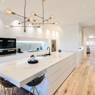 Photo of a contemporary eat-in kitchen in Adelaide with an undermount sink, flat-panel cabinets, white cabinets, white splashback, stainless steel appliances, light hardwood floors, with island, beige floor and white benchtop.
