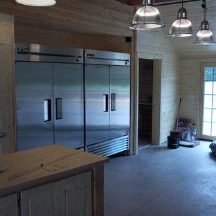 他の地域の大きいラスティックスタイルのおしゃれなキッチン (ダブルシンク、フラットパネル扉のキャビネット、中間色木目調キャビネット、木材カウンター、メタリックのキッチンパネル、メタルタイルのキッチンパネル、シルバーの調理設備、コンクリートの床) の写真