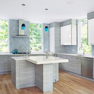 Contemporary kitchen designs - Inspiration for a contemporary light wood floor and beige floor kitchen remodel with an undermount sink, flat-panel cabinets, white cabinets, blue backsplash, matchstick tile backsplash, stainless steel appliances, an island and white countertops