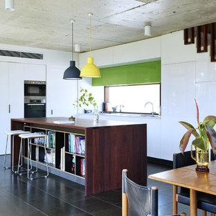Foto de cocina en L, vintage, abierta, con armarios con paneles lisos, puertas de armario blancas, encimera de madera, electrodomésticos de acero inoxidable y una isla