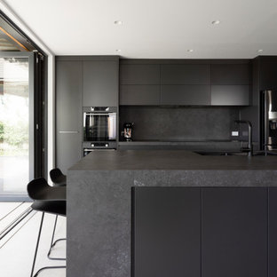 Inspiration for a mid-sized contemporary galley open plan kitchen in Sydney with an undermount sink, grey floor, grey cabinets, solid surface benchtops, grey splashback, stone slab splashback, black appliances, cement tiles, with island and grey benchtop.