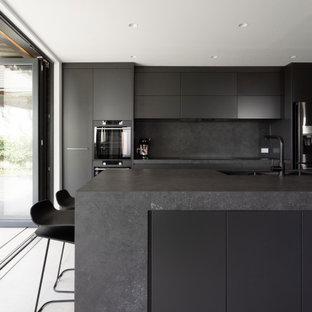 Idéer för att renovera ett mellanstort funkis grå grått kök, med en undermonterad diskho, grått golv, grå skåp, bänkskiva i koppar, grått stänkskydd, stänkskydd i sten, svarta vitvaror, cementgolv och en köksö