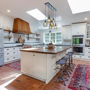 Diseño de cocina en L, de estilo de casa de campo, con fregadero sobremueble, armarios estilo shaker, puertas de armario blancas, salpicadero blanco, salpicadero de ladrillos, electrodomésticos de acero inoxidable, suelo de ladrillo, una isla, suelo rojo y encimeras negras