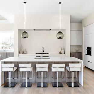 Large contemporary eat-in kitchen designs - Large trendy light wood floor and beige floor eat-in kitchen photo in DC Metro with an undermount sink, flat-panel cabinets, white cabinets, quartz countertops, white backsplash, an island and paneled appliances