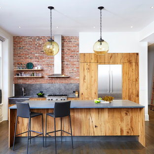 Inspiration for an industrial galley medium tone wood floor and brown floor open concept kitchen remodel in New York with flat-panel cabinets, marble countertops, stainless steel appliances, an island, a farmhouse sink, medium tone wood cabinets and gray backsplash
