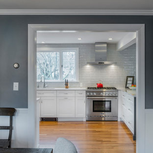 Mid-sized transitional eat-in kitchen ideas - Eat-in kitchen - mid-sized transitional l-shaped light wood floor and brown floor eat-in kitchen idea in Boston with an undermount sink, white cabinets, quartz countertops, gray backsplash, ceramic backsplash, stainless steel appliances, a peninsula and shaker cabinets