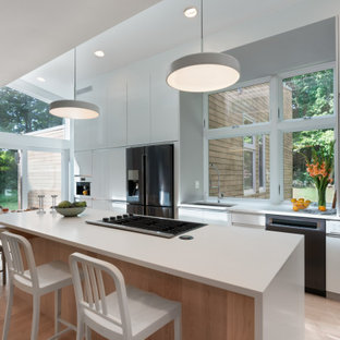 Mid-sized modern open concept kitchen ideas - Example of a mid-sized minimalist single-wall light wood floor open concept kitchen design in Boston with a single-bowl sink, flat-panel cabinets, white cabinets, quartz countertops, glass sheet backsplash, black appliances, an island and white countertops