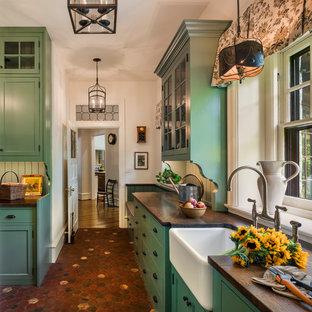 Modelo de cocina tradicional, cerrada, con fregadero sobremueble, armarios estilo shaker, puertas de armario verdes, suelo de baldosas de terracota, suelo rojo y encimera de madera