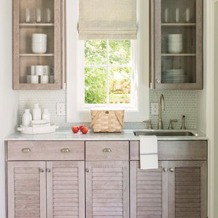 Design ideas for a traditional galley kitchen in DC Metro with louvered cabinets, grey cabinets, white splashback, subway tile splashback, stainless steel appliances and brown floor.