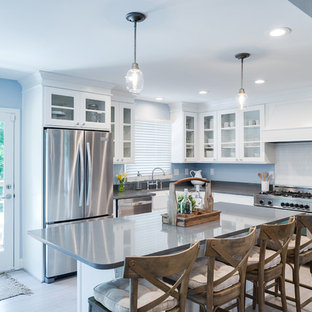 Photo of a country l-shaped eat-in kitchen in New York with a farmhouse sink, flat-panel cabinets, white cabinets, white splashback, subway tile splashback, stainless steel appliances, light hardwood floors, with island, beige floor and grey benchtop.