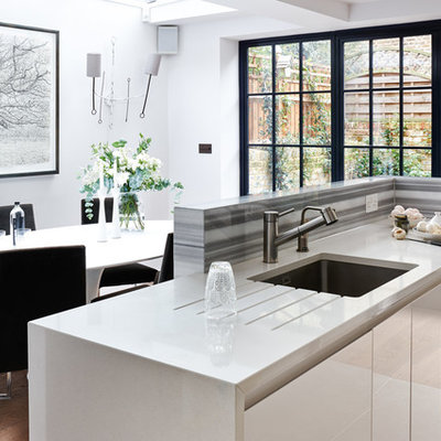 Example of a small minimalist galley medium tone wood floor eat-in kitchen design in London with an integrated sink, flat-panel cabinets, white cabinets, solid surface countertops, gray backsplash, glass sheet backsplash, stainless steel appliances, an island and white countertops
