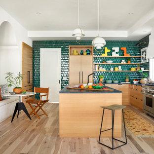 Exemple d'une grande cuisine américaine éclectique en L avec un placard à porte plane, des portes de placard en bois clair, un plan de travail en stéatite, un îlot central, une crédence verte, une crédence en carreau de verre, un électroménager encastrable, un sol en bois clair, un sol gris et un plan de travail gris.