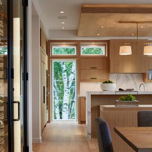 Modelo de cocina comedor moderna con armarios con paneles lisos, puertas de armario de madera clara, encimera de mármol, salpicadero blanco, salpicadero de losas de piedra, electrodomésticos con paneles, suelo de madera clara y dos o más islas