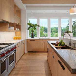 Modern eat-in kitchen in Minneapolis with flat-panel cabinets, light wood cabinets, marble benchtops, white splashback, stone slab splashback, panelled appliances, light hardwood floors and multiple islands.