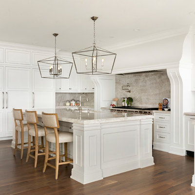 Inspiration for a timeless u-shaped medium tone wood floor and brown floor kitchen remodel in Minneapolis with an undermount sink, recessed-panel cabinets, white cabinets, beige backsplash, stone slab backsplash, paneled appliances, an island and beige countertops