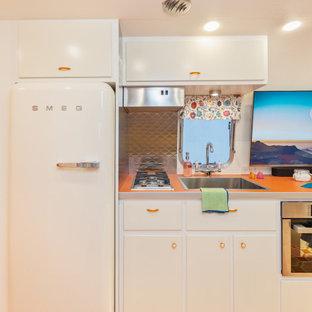 Diseño de cocina bohemia, pequeña, con armarios con paneles lisos, puertas de armario blancas, encimera de laminado, salpicadero metalizado, electrodomésticos blancos, suelo de madera pintada, suelo naranja y encimeras naranjas