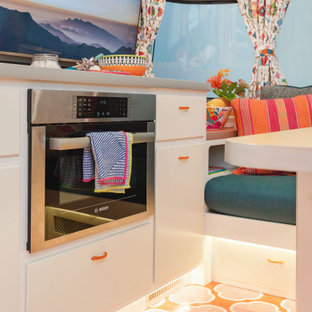 This is an example of a small eclectic kitchen in Los Angeles with flat-panel cabinets, white cabinets, laminate benchtops, metallic splashback, white appliances, painted wood floors, orange floor and orange benchtop.