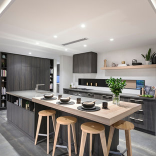 Design ideas for a contemporary l-shaped kitchen in Perth with an undermount sink, flat-panel cabinets, dark wood cabinets, panelled appliances, with island, grey floor and grey benchtop.