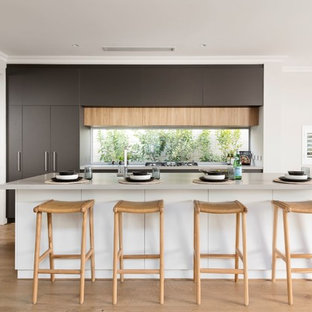 Design ideas for a contemporary galley kitchen in Perth with flat-panel cabinets, grey cabinets, window splashback, light hardwood floors, with island, brown floor and white benchtop.