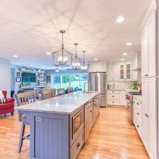 セントルイスのエクレクティックスタイルのおしゃれなキッチン (アンダーカウンターシンク、シェーカースタイル扉のキャビネット、白いキャビネット、クオーツストーンカウンター、グレーのキッチンパネル、サブウェイタイルのキッチンパネル、シルバーの調理設備、無垢フローリング、茶色い床、マルチカラーのキッチンカウンター) の写真