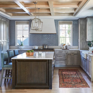 Design ideas for a transitional u-shaped kitchen in Chicago with a farmhouse sink, recessed-panel cabinets, grey cabinets, grey splashback, glass tile splashback, stainless steel appliances, light hardwood floors, with island, beige floor, white benchtop, exposed beam and wood.