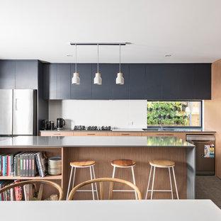 パースの中くらいのビーチスタイルのおしゃれなキッチン (アンダーカウンターシンク、フラットパネル扉のキャビネット、中間色木目調キャビネット、白いキッチンパネル、ガラスまたは窓のキッチンパネル、シルバーの調理設備、グレーの床、グレーのキッチンカウンター) の写真
