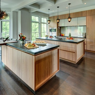 This is an example of a large contemporary eat-in kitchen in New York with an undermount sink, flat-panel cabinets, medium wood cabinets, white splashback, glass sheet splashback, panelled appliances, dark hardwood floors and multiple islands.