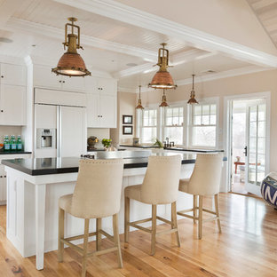 Example of an ornate kitchen design in Providence with a farmhouse sink, shaker cabinets, white cabinets and paneled appliances