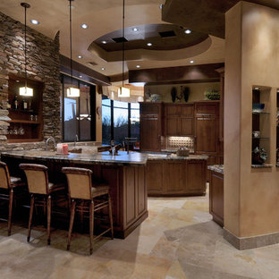 Southwestern kitchen pictures - Kitchen - southwestern kitchen idea in Phoenix with raised-panel cabinets, dark wood cabinets, beige backsplash and paneled appliances