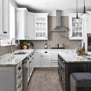 Immagine di una cucina a L chic con lavello sottopiano, ante di vetro, ante bianche, paraspruzzi grigio, elettrodomestici in acciaio inossidabile, isola e pavimento grigio