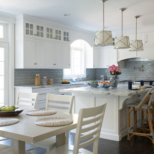 Mid-sized transitional eat-in kitchen remodeling - Mid-sized transitional u-shaped dark wood floor and brown floor eat-in kitchen photo in New York with a farmhouse sink, shaker cabinets, white cabinets, gray backsplash, an island, marble countertops, subway tile backsplash, stainless steel appliances and gray countertops