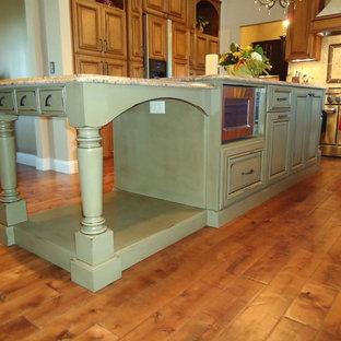 セントルイスの大きいカントリー風おしゃれなキッチン (ダブルシンク、レイズドパネル扉のキャビネット、茶色いキャビネット、御影石カウンター、ベージュキッチンパネル、セラミックタイルのキッチンパネル、シルバーの調理設備、濃色無垢フローリング、茶色い床) の写真