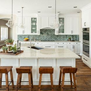 Bild på ett mellanstort vintage vit vitt kök, med en undermonterad diskho, skåp i shakerstil, vita skåp, bänkskiva i kvartsit, blått stänkskydd, stänkskydd i terrakottakakel, rostfria vitvaror, mörkt trägolv, en köksö och brunt golv