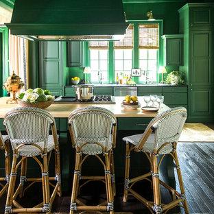 タンパの大きいヴィクトリアン調のおしゃれなキッチン (レイズドパネル扉のキャビネット、緑のキャビネット、木材カウンター、パネルと同色の調理設備、塗装フローリング、黒い床、茶色いキッチンカウンター) の写真