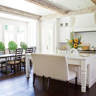 Foto de cocina comedor de estilo de casa de campo con armarios con paneles con relieve, puertas de armario blancas, salpicadero blanco, salpicadero de azulejos tipo metro, suelo de madera oscura, una isla y suelo marrón