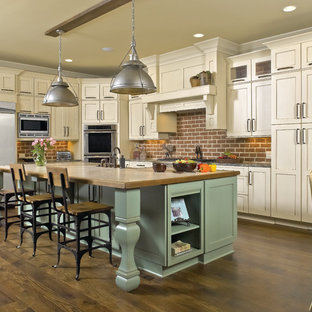Mid-sized farmhouse open concept kitchen designs - Inspiration for a mid-sized cottage u-shaped dark wood floor and brown floor open concept kitchen remodel in Chicago with a farmhouse sink, shaker cabinets, brick backsplash, stainless steel appliances, beige cabinets, wood countertops, red backsplash and an island