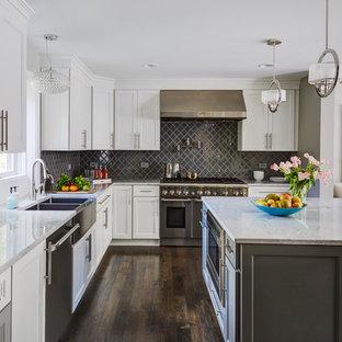 Große Klassische Wohnküche in U-Form mit Landhausspüle, Schrankfronten mit vertiefter Füllung, weißen Schränken, Marmor-Arbeitsplatte, Küchenrückwand in Grau, Rückwand aus Porzellanfliesen, Küchengeräten aus Edelstahl, dunklem Holzboden, Kücheninsel und braunem Boden in Chicago