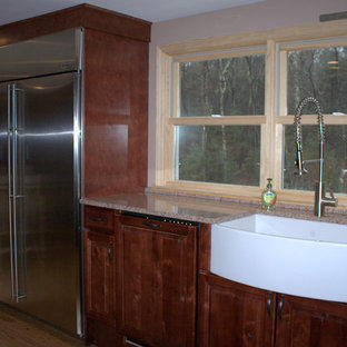 Inspiration for a mid-sized farmhouse u-shaped medium tone wood floor eat-in kitchen remodel in Boston with a farmhouse sink, raised-panel cabinets, medium tone wood cabinets, quartz countertops, beige backsplash, paneled appliances and no island