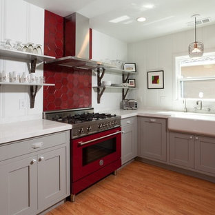 Mid-sized trendy u-shaped medium tone wood floor eat-in kitchen photo in Sacramento with a farmhouse sink, shaker cabinets, gray cabinets, red backsplash, stainless steel appliances and no island
