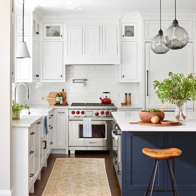 Beach style l-shaped dark wood floor kitchen photo in Boston with shaker cabinets, white cabinets, white backsplash, a farmhouse sink, subway tile backsplash, stainless steel appliances, an island and white countertops