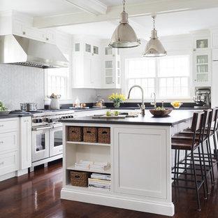 Cette photo montre une cuisine bord de mer en L avec un placard à porte shaker, des portes de placard blanches, une crédence grise, un électroménager en acier inoxydable, un sol en bois foncé et un îlot central.