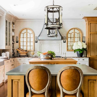 This is an example of a large traditional l-shaped eat-in kitchen in Boston with beaded inset cabinets, medium hardwood floors, multiple islands, white splashback, a farmhouse sink, white cabinets, zinc benchtops, subway tile splashback, stainless steel appliances and brown floor.