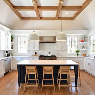 Inredning av ett modernt stort, avskilt u-kök, med en undermonterad diskho, vita skåp, bänkskiva i kvarts, vitt stänkskydd, stänkskydd i keramik, rostfria vitvaror, mellanmörkt trägolv, en köksö, brunt golv och skåp i shakerstil