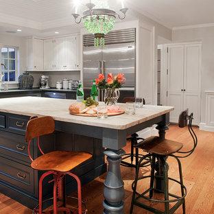 Cette photo montre une grande cuisine victorienne en L avec un évier encastré, un placard avec porte à panneau surélevé, des portes de placard en bois sombre, un plan de travail en marbre, une crédence rouge, une crédence en brique, un électroménager en acier inoxydable, un sol en bois brun, un îlot central et un sol marron.